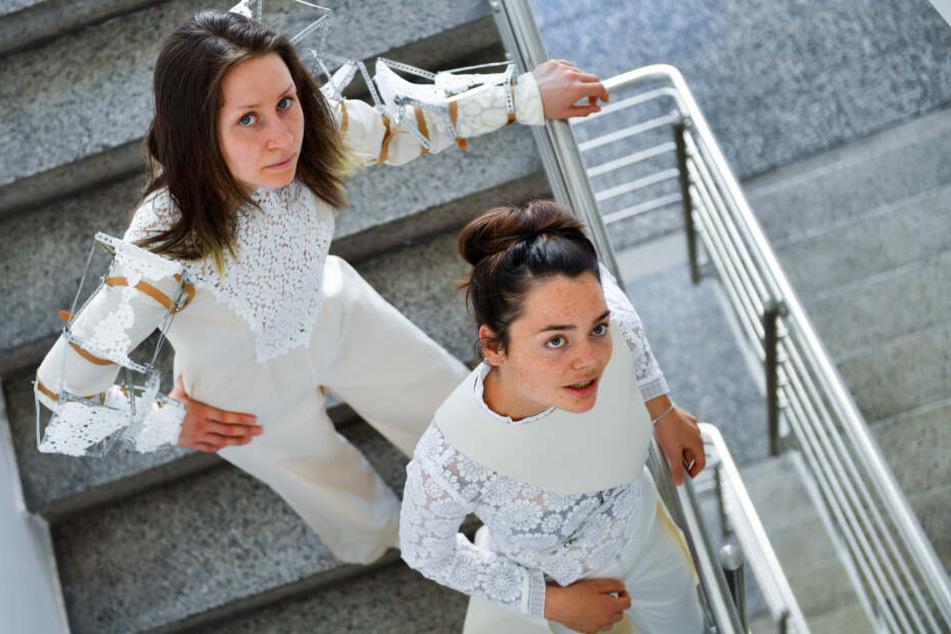 Die Modedesign-Studentinnen Pauline Kuhn (l.) und Juliane Mann tragen zwei Outfits mit Stickereien aus Plauener Spitze ihrer Kommilitoninnen Thuy Tien Phan (linker Entwurf) und Anna Reichardt.