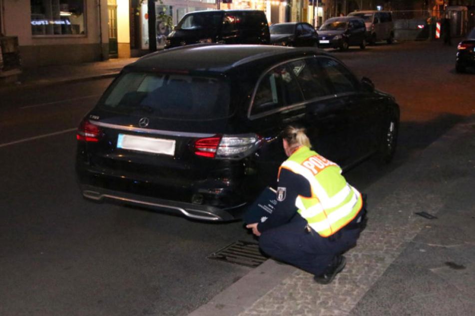 Eine Polizistin begutachtet den Mercedes.