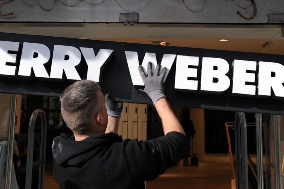 """Ein Monteur hängt ein Schild mit dem Schriftzug """"Gerry Weber"""" an einer geschlossenen Filiale der Modemarke ab"""