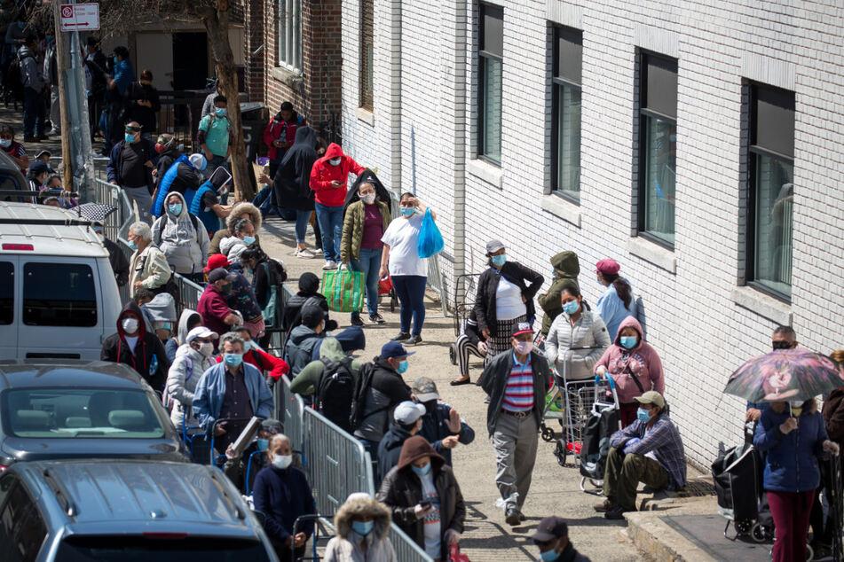 Menschen stehen Schlange vor einer Lebensmittelausgabe für Bedürftige im New Yorker Stadtteil Brooklyn. Seit Mitte März haben in den USA bereits Millionen Menschen mindestens zeitweise ihren Job verloren.