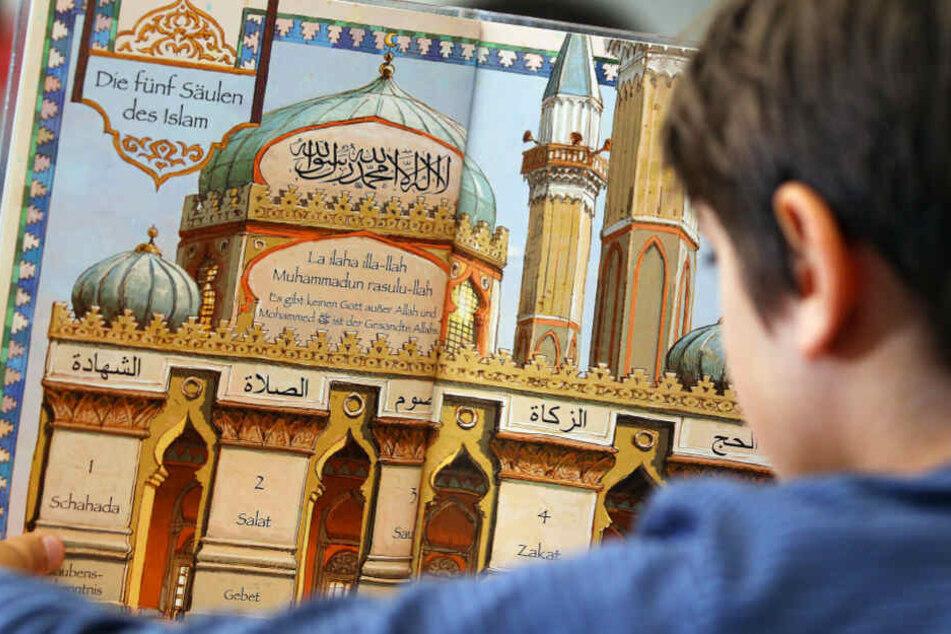 Das Bild aus dem Juni 2018 zeigt ein Jungen, der während des islamischen Religionsunterrichts in einem Schulbuch liest.