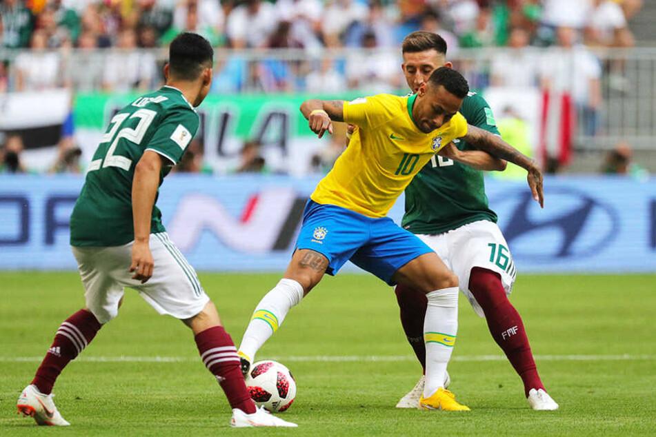 Mit neuer Frisur: Brasiliens Superstar Neymar (M.) muss sich der harten Gegenwehr der Mexikaner Hirving Lozano (l.) und Héctor Herrera (hinten) erwehren.