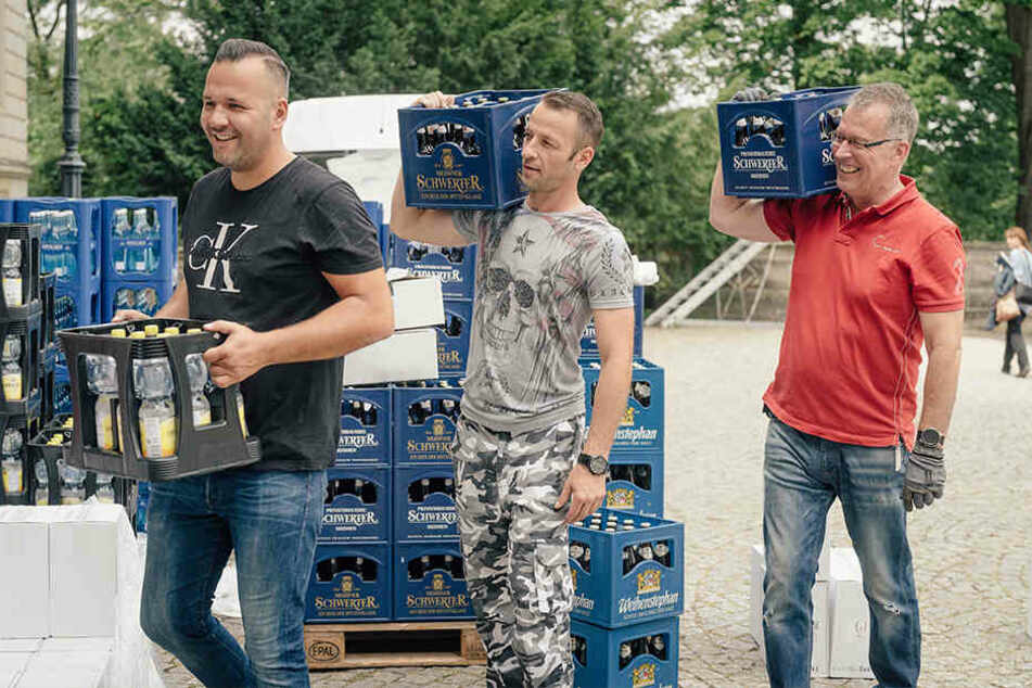 Lars Hauptvogel (31, v.l.), Sebastian Brohst (37) und Burkhard Hille (50) schleppen Getränkekästen ins Schloss Albrechtsberg. Eine Sackkarre darf aus Denkmalschutzgründen nicht benutzt werden.