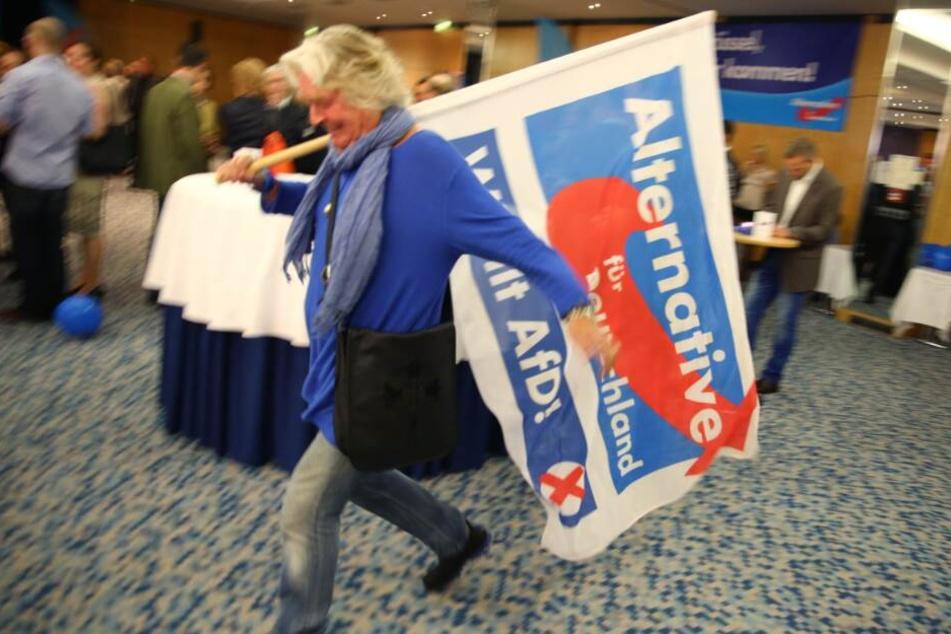 Eine Anhängerin der AfD schwingt eine Fahne ihrer Partei.