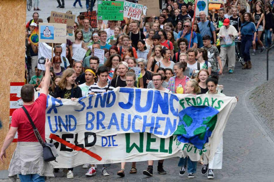 """Teilnehmer einer Fridays for Future-Demonstration halten ein Banner mit der Aufschrift """"Wir sind jung, wir brauchen die Welt""""."""