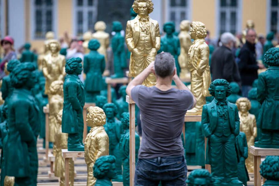 Ein Besucher fotografiert die Beethoven-Skulpturen in Bonn.