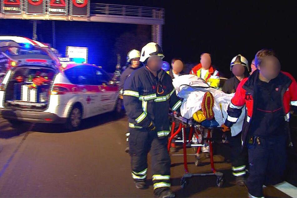 Helfer bringen einen Schwerverletzten zum Rettungswagen. Sie mussten zu Fuß zur Unfallstelle.