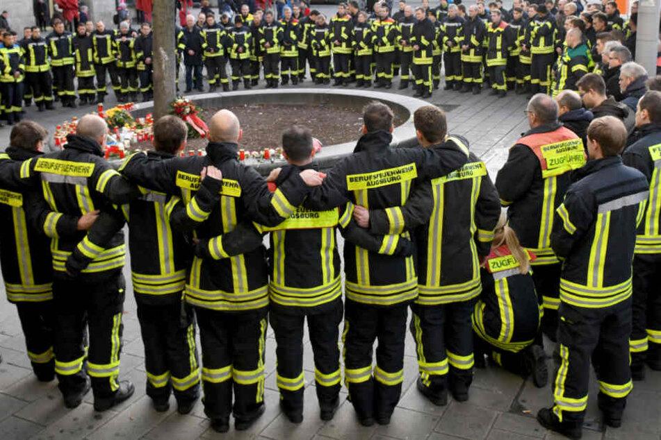 Feuerwehrleute trauern am Augsburger Königsplatz, nachdem ein 49-Jähriger hier attackiert und später verstorben war.