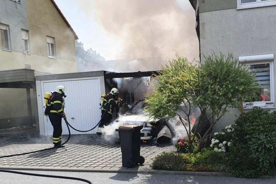 Feuerwehrleute löschen ein brennendes Auto.