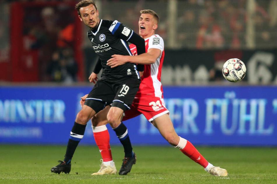 Manuel Prietl von Arminia Bielefeld (l) kämpft mit Berlins Grischa Prömel um den Ball.