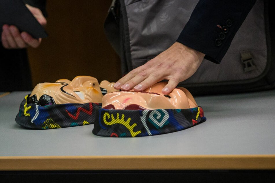 Ein Angeklagter legt zwei Hexenmasken im Amtsgericht Heilbronn auf den Tisch.