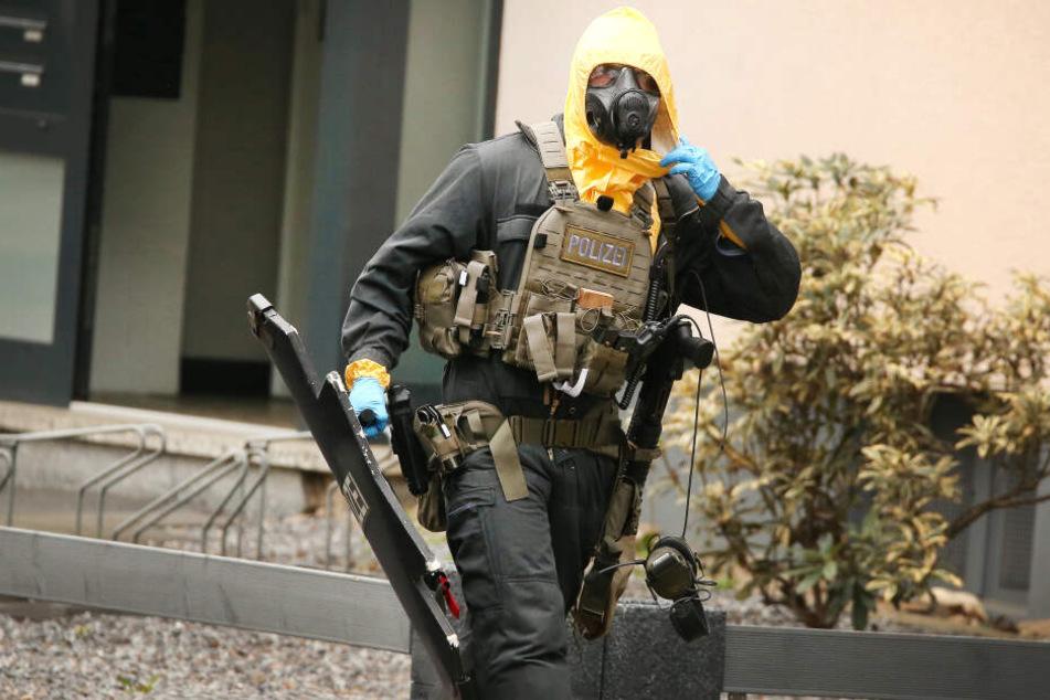 Ein Beamter des Spezialeinsatzkommandos läuft aus dem Haus.