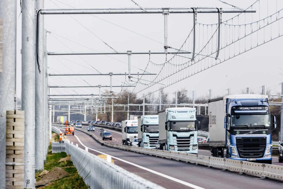 Lastwagen fahren auf der Autobahn 1 an neu installierten Oberleitungssystemen vorbei.