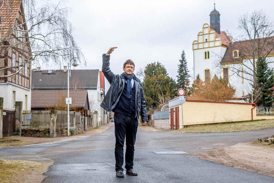 Der Coswiger Ordnungsamtsleiter Olaf Lier (56) vor Ort in Brockwitz: Die Häuser auf der tieferen Dorfseite (links) müssten angehoben werden, die Gebäude oberhalb der Kirche (rechts) liegen bereits hoch genug und flutsicher.
