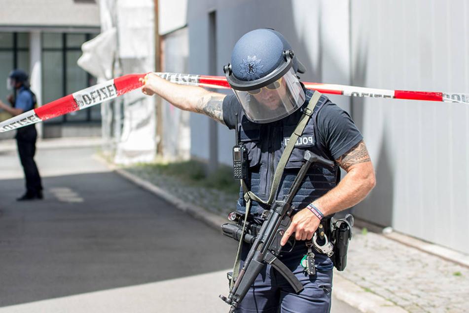 Ein mit einer Maschinenpistole bewaffneter Polizist bewegt sich durch eine Absperrung am Anger. Der Einsatz von ihm und seinen Kollegen könnte nun richtig teuer werden.
