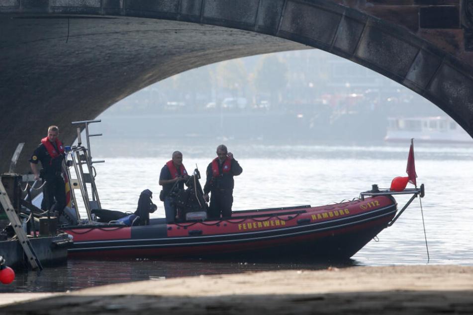 Einsatzkräfte des Kampfmittelräumdienstes stehen bei der Bergung einer Weltkriegsgranate im Bereich der Lombardsbrücke in einem Boot. (Archivbild)