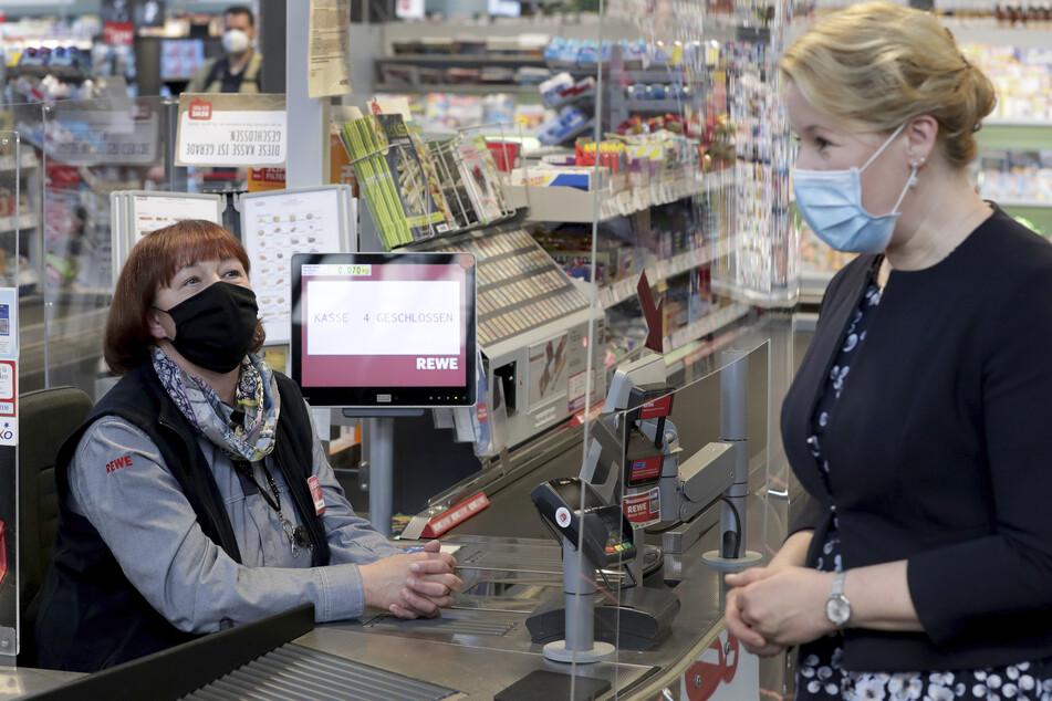 Kassiererin Kerstin Strasen (l) sitzt an einer Kasse in einem Supermarkt in Berlin.