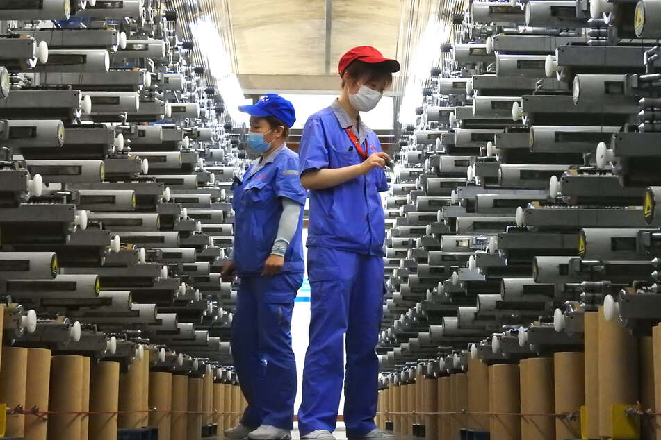 Arbeiter überprüfen eine Produktionslinie im Lianyungang Economic and Technological Development Area in Lianyungang in der ostchinesischen Provinz Jiangsu.