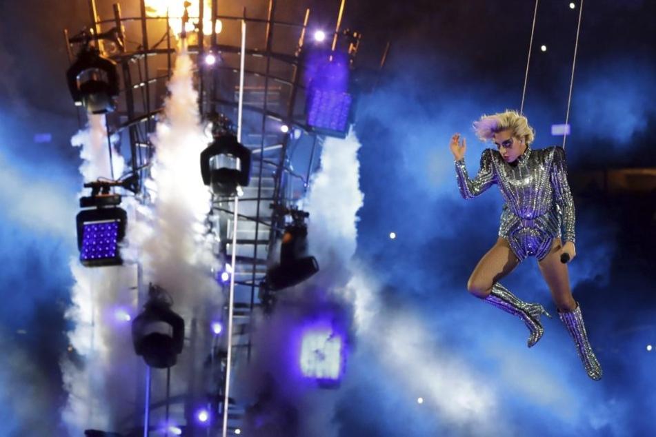 Nach einem patriotischen Appell geht es gleich weider mit der typischen Gaga-Show. Hier lässt sie sich vom Dach auf einen brennenden Turm abseilen.