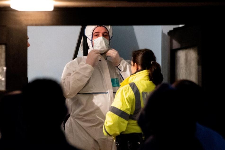 Ein Beamter der Spurensicherung steht im Flur eines Mehrfamilienhauses neben einer Polizistin.