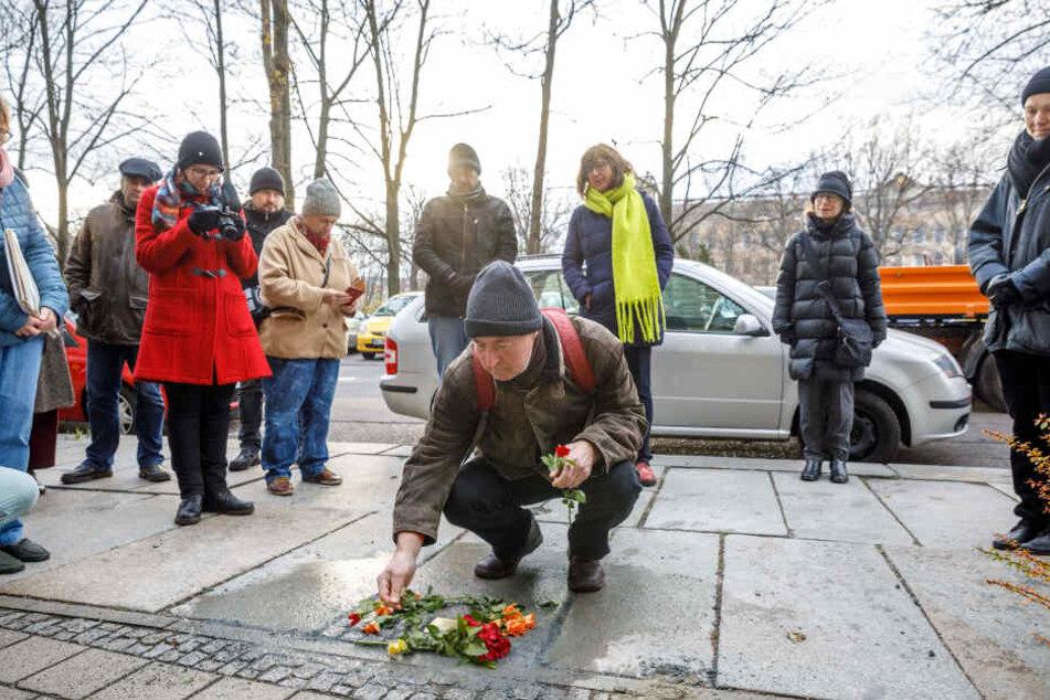 Matthias Krause (67, aus Weimar) legt eine Rose nieder.