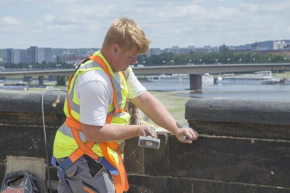 Ein Bauarbeiter hämmert an der Brüstung der Augustusbrücke.