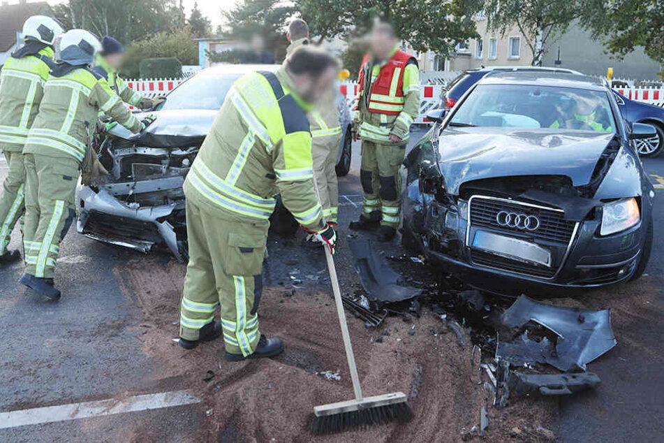 Feuerwehrleute beseitigen auf der Kreuzung Radeburger Straße/Ludwig-Kossuth-Straße ausgetretene Betriebsstoffe.