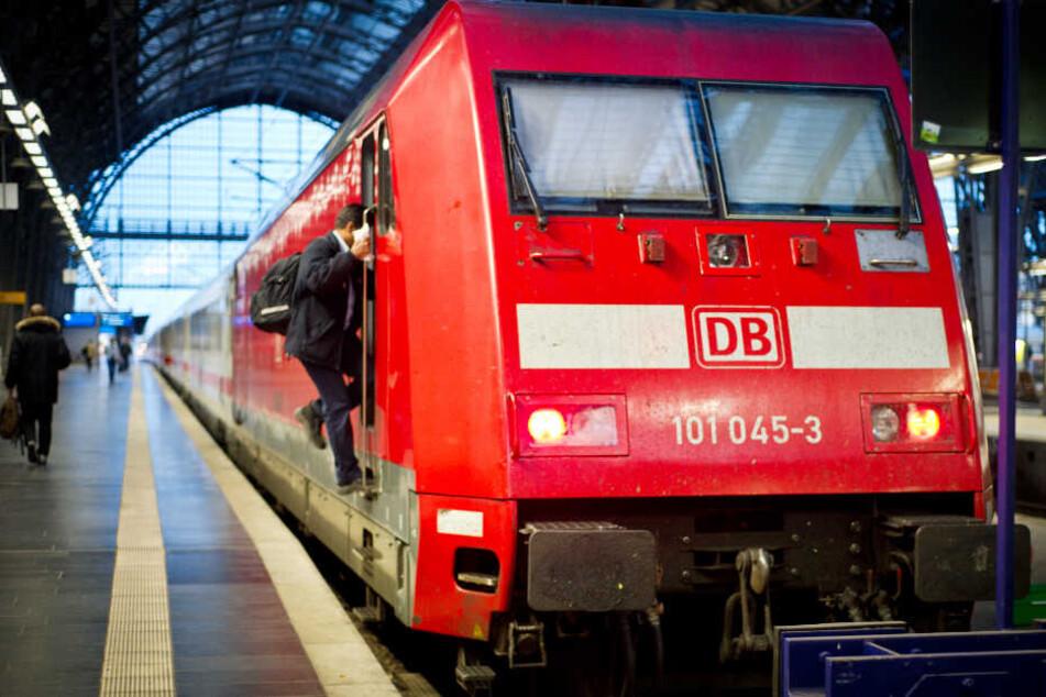 Ein Zug steht abfahrbereit in einem Bahnhof. Auf den Puffern (vorne) der Lok sind zwei Jugendliche gesurft (Symbolbild).
