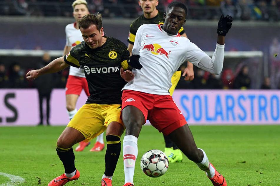 BVB-Star Mario Götze (l.) versucht, sich gegen RB Leipzigs Abwehrkante Ibrahima Konaté (r.) durchzusetzen.