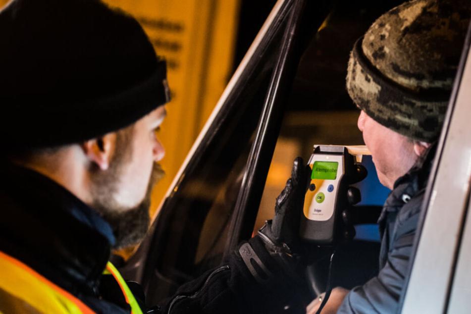 Ein Polizist führt bei einem Lkw-Fahrer eine Alkoholkontrolle durch.