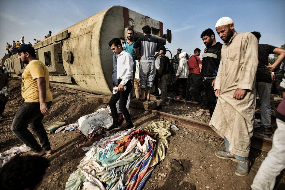 Menschen stehen vor einem umgekippten Waggon des verunglückten Zugs.