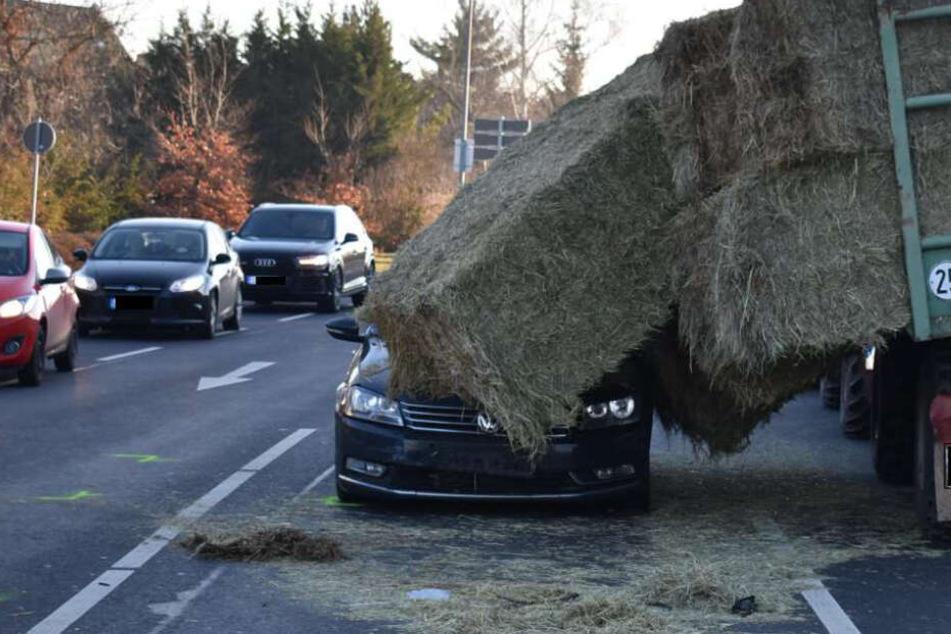 Riesige Heuballen rutschen während der Fahrt von Traktor auf Autos