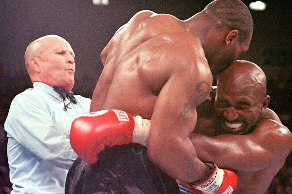 Der Weltmeister im Schwergewicht, Evander Holyfield (r), verzieht am 28.06.1997 in Las Vegas das Gesicht, nachdem ihn sein Herausforderer Mike Tyson (M) ins Ohr gebissen hat. Der Ringrichter Lane Mills (l) unterbricht in diesem Moment den Kampf.