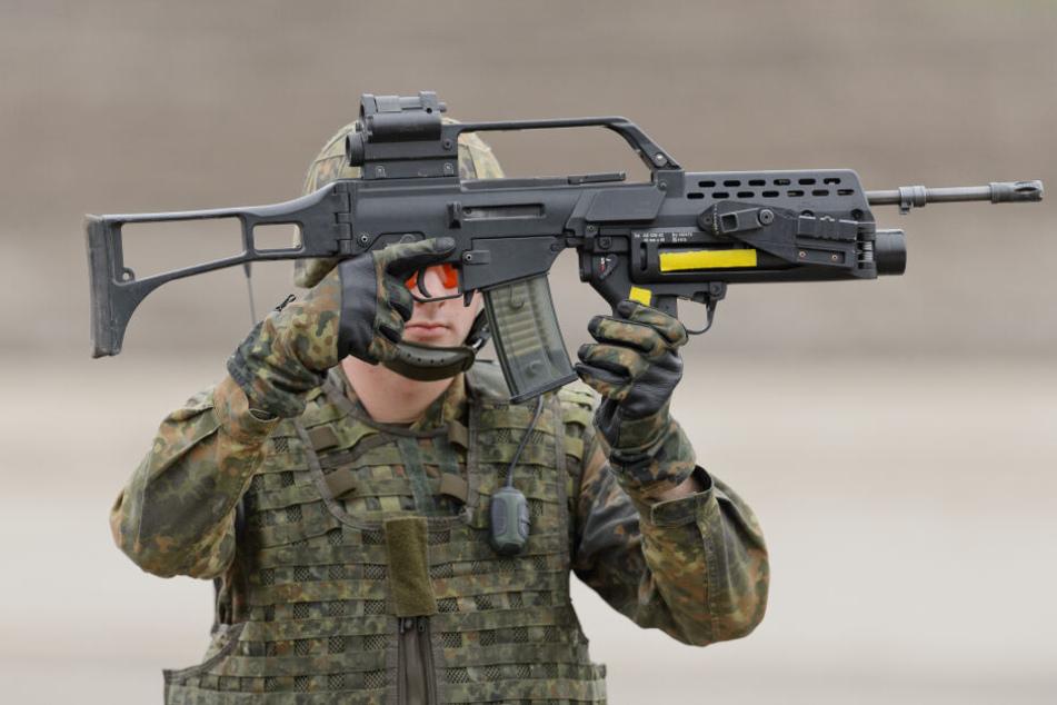 Ein Soldat der Bundeswehr hält ein Gewehr G36 der Firma Heckler & Koch modifiziert mit einem Abschussgerät für Granaten in der Hand.