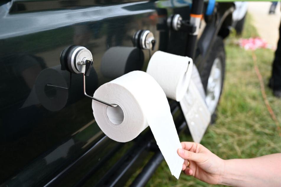 Ein Messebesucher zieht an einer Toilettenpapierrolle, die an einem Saugnapf befestigt ist.