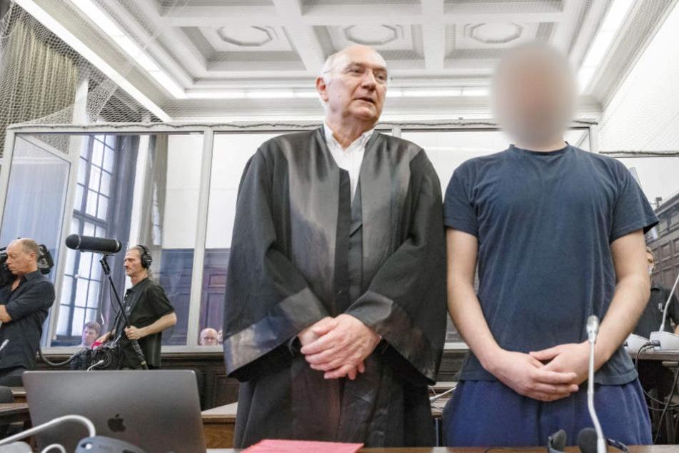 Der Angeklagte Yamen A. steht im Gerichtssaal neben seinem Verteidiger.