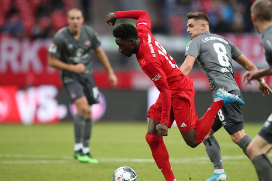 Alphonso Davies spielt den Ball vor seinem Treffer zum 1:1 neben den beiden Nürnbergern Nikola Dovedan (2.v.r.) und Lukas Jäger (r).