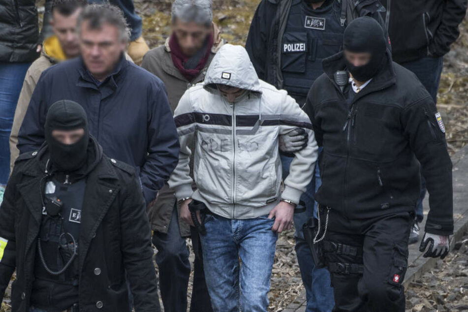 Ali B. geht flankiert von zwei maskierten Polizeibeamten die Eisenbahnstrecke entlang, an der er die 14-Jährige Susanna umgebracht haben soll (Archivbild).