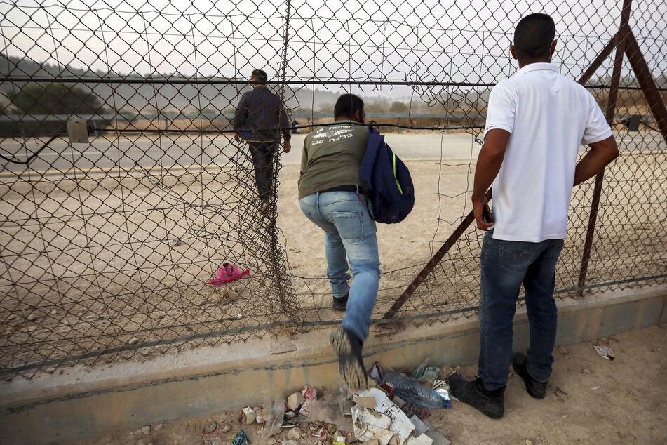 Palästinensische Arbeiter überqueren illegal aus dem Westjordanland durch ein Loch in einem Zaun die Grenze nach Israel.