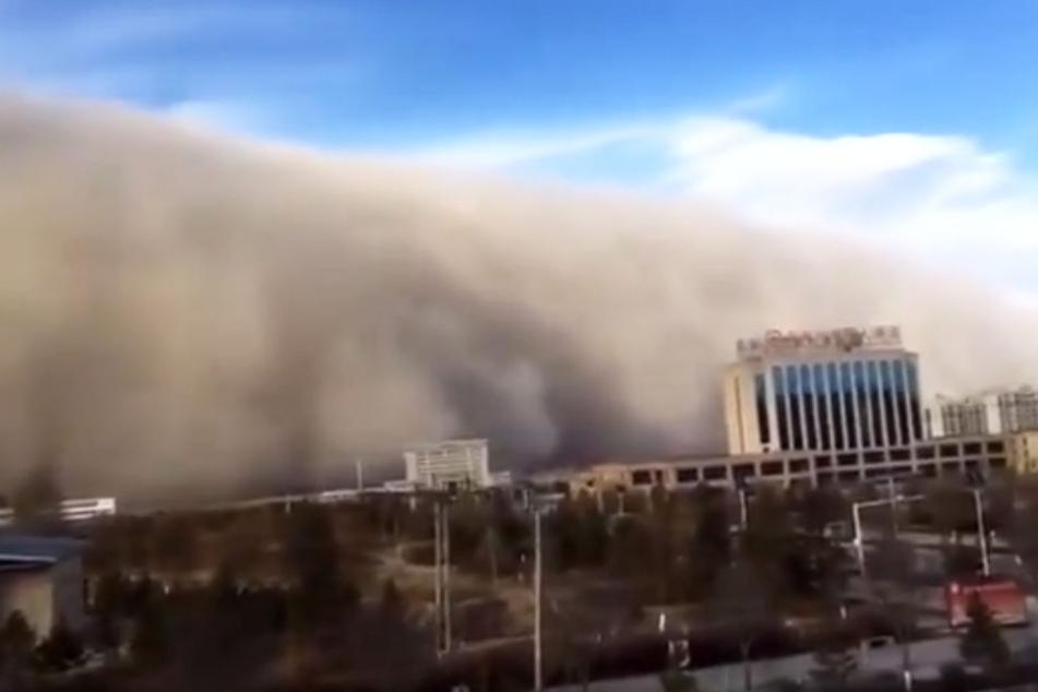 Wie eine graue Wand baute sich der Sandsturm vor der Stadt auf.