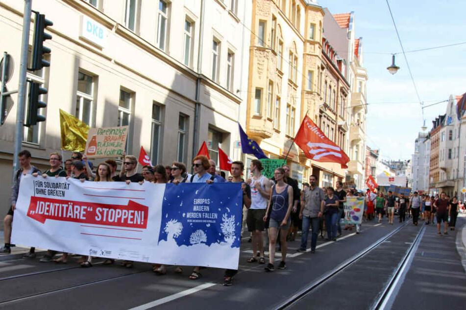 Mit Transparenten ziehen die Gegendemonstranten durch die Hallesche Innenstadt.
