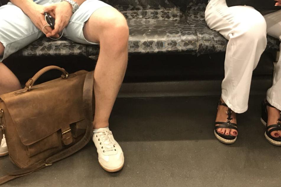 Ein Mann sitzt breitbeinig in der U-Bahn, während sich die Frau von ihm weglehnt.