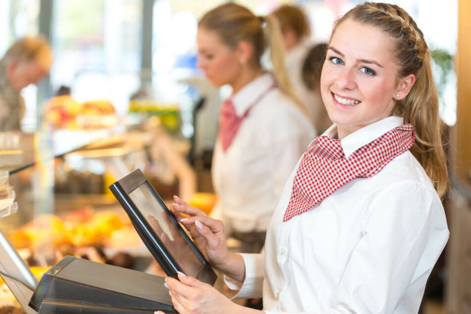 Eine junge Auszubildende lächelt an der Verkaufstheke einer Bäckerei in die Kamera. Der Einzelhandel sucht noch dringend neue Lehrlinge.