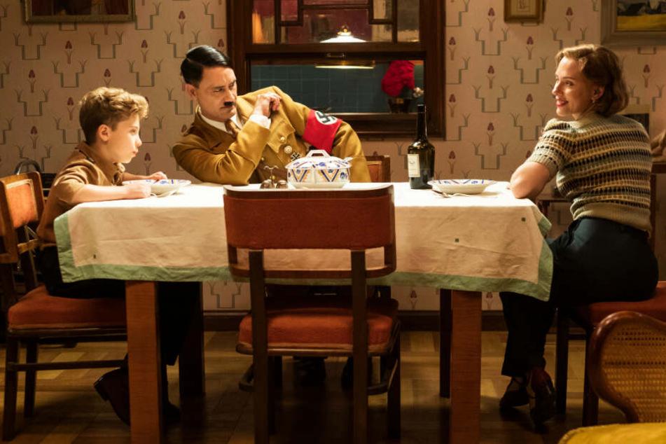 Jojo Rabbit (l., Roman Griffin Davis) hat seinen unsichtbaren Freund Adolf Hitler (M., Taika Waititi) immer dabei - auch beim Essen mit seiner Mutter Rosie (Scarlett Johansson).