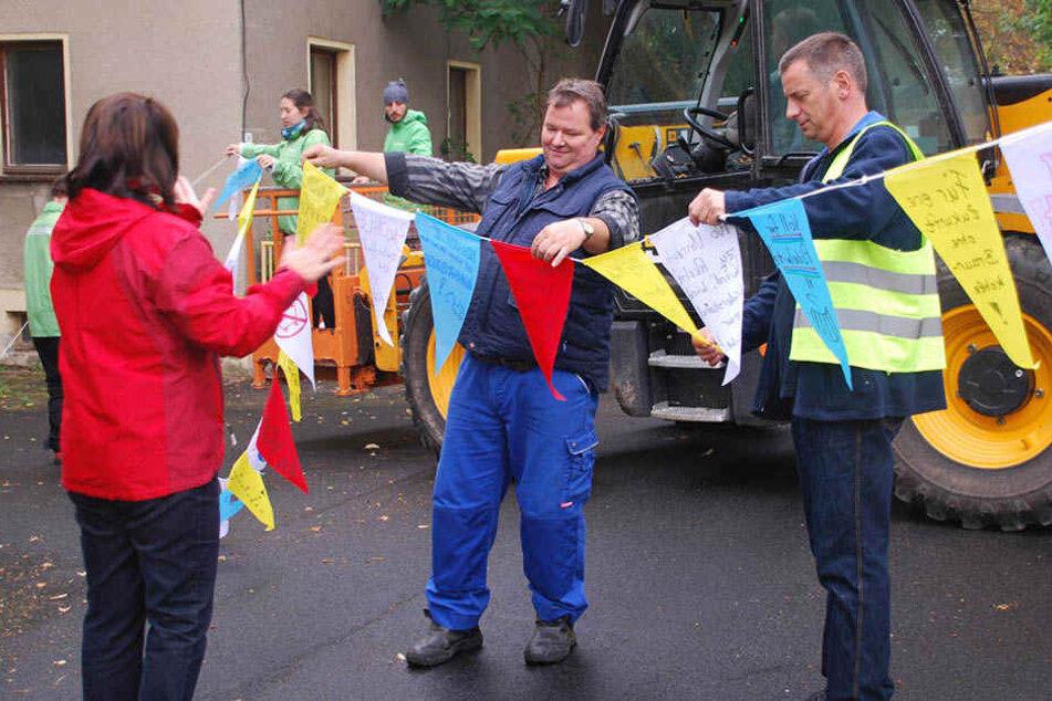 Dorfbewohner und Greenpeace-Aktivisten hängen bunte Wimpel mit Botschaften über den Straßen von Pödelwitz auf.