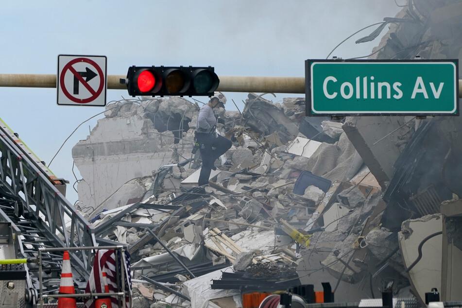 Eine Rettungskraft der Feuerwehr geht durch die Trümmer einer Unfallstelle. Bei dem Teileinsturz eines mehrstöckigen Wohnhauses nahe Miami Beach ist mindestens ein Mensch ums Leben gekommen.