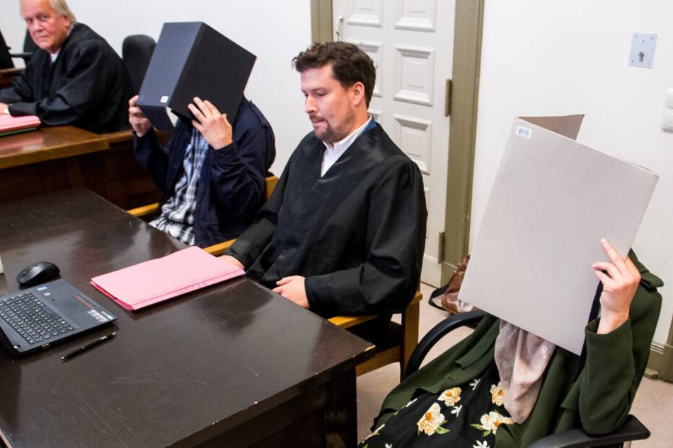 Die Eltern verstecken ihre Gesichter im Gerichtssaal hinter Ordnern.