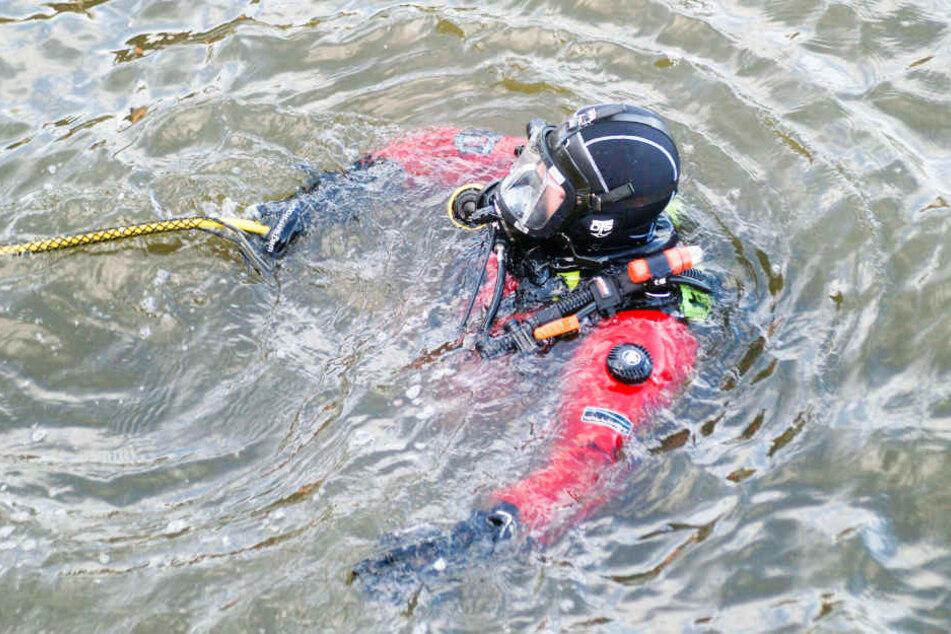 Taucher der Feuerwehr suchen am Grund der Elbe nach dem Vermissten.