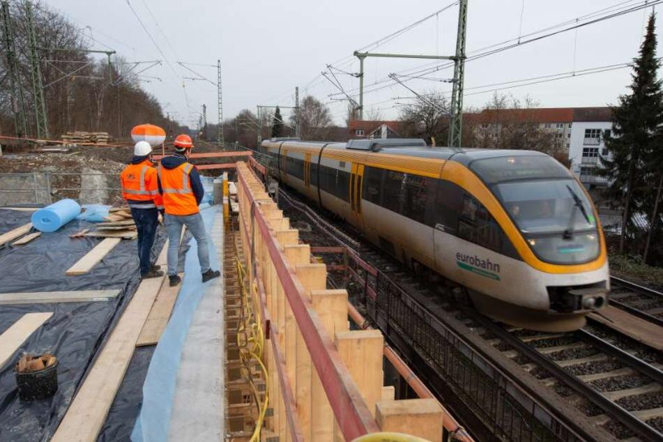 Ein Zug der Eurobahn fährt über eine zum Teil eingeschalte und gesperrte Bahnbrücke.