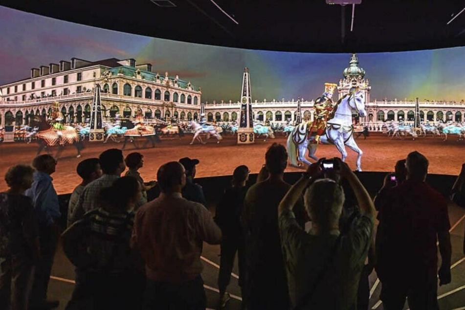 Auf einer beeindruckenden Leinwand wird die Superhochzeit gezeigt.